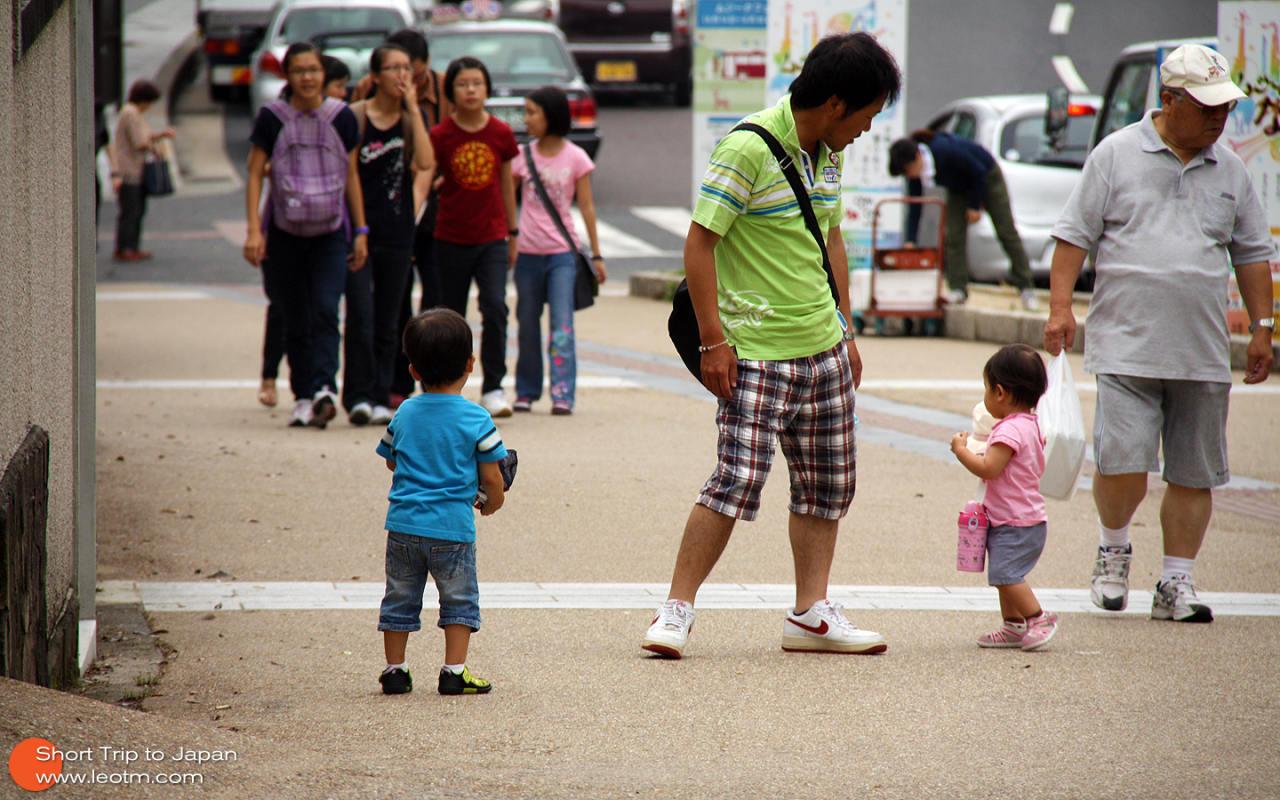 带着两个孩子出来玩的父亲。小女儿闹脾气不想自己走,父亲一开始不同意,后来让步接过了她的水壶,她立马高兴的走起来。在日本,孩子是被要求要做所有力所能及的事情的。